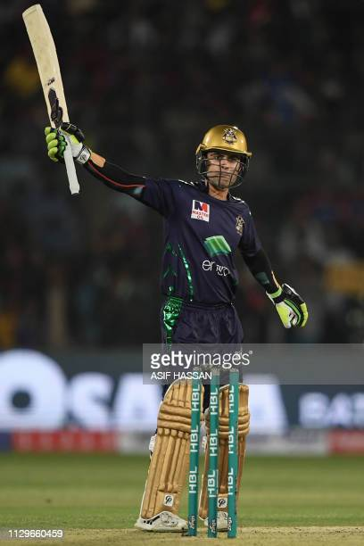 Cricketer Ahmed Shahzad of Quetta Gladiators wave his bat after makes fifty runs in the National Cricket Stadium during the second match of the last...