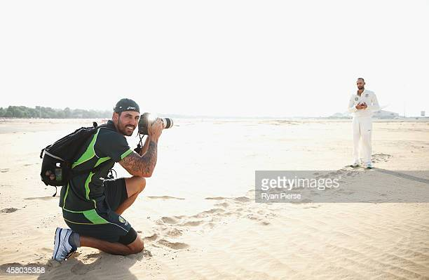 Cricketer and photography student Mitchell Johnson of Australia takes pictures of Nathan Lyon of Australia as he poses outisde Sheikh Zayed Cricket...