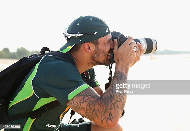 Cricketer and photography student Mitchell Johnson of Australia takes pictures of Nathan Lyon of Australia as he poses outside Sheikh Zayed Cricket...