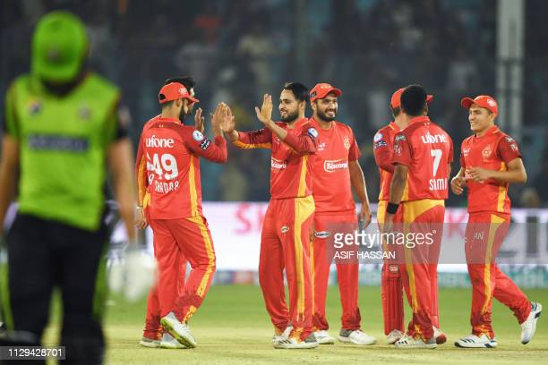 Cricketer Faheem Ashraf of Islamabad United celebrates with teammates after bowled to Shaheen Shah Afridi of Lahore Qalandars going back to pavilion...