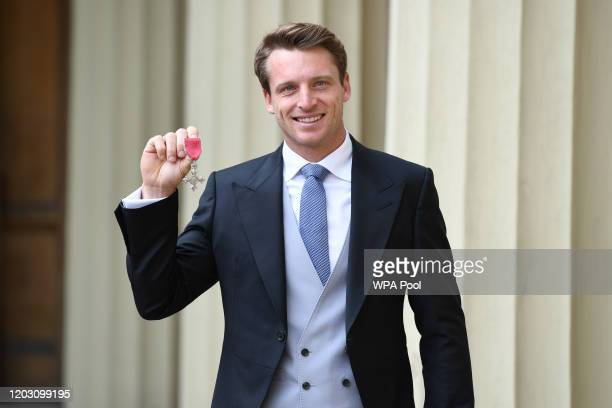 Cricketer Jos Buttler holds up his MBE for services to cricket following an investiture ceremony at Buckingham Palace on February 25, 2020 in London,...