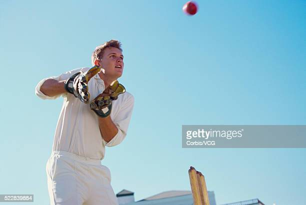 A cricketer preparing to catch the ball