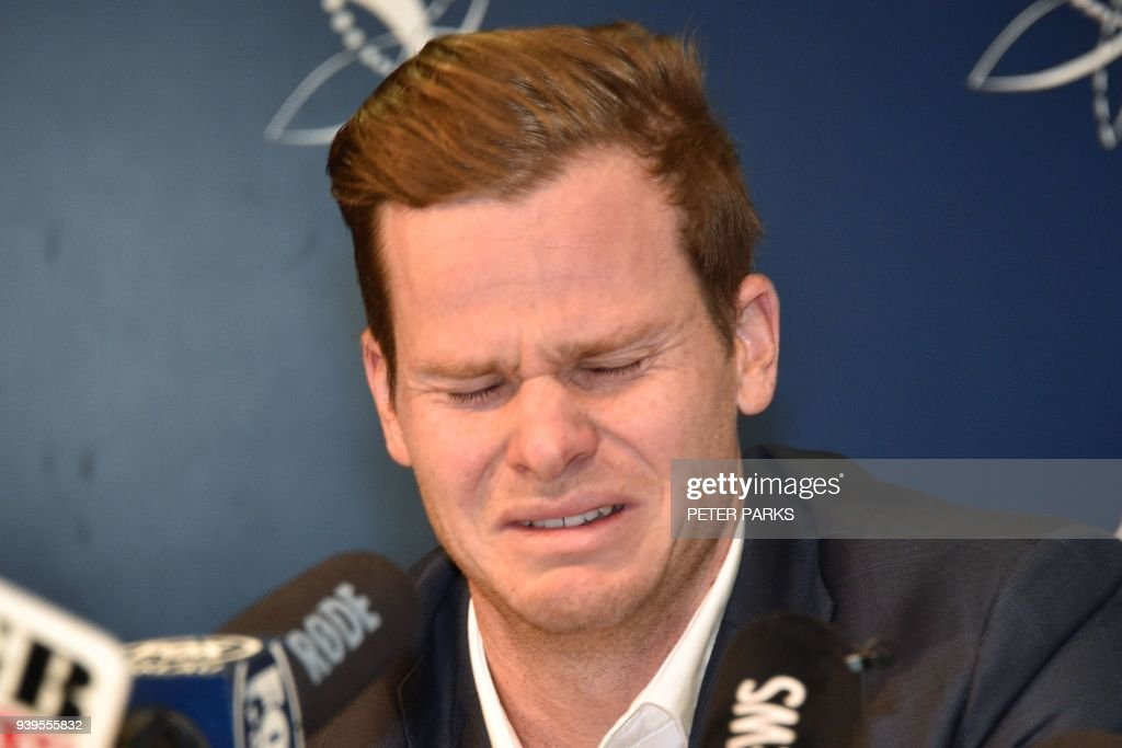 TOPSHOT - Cricketer Steve Smith reacts at a press conference at the airport in Sydney on March 29, 2018, after returning from South Africa. Distraught Australian cricketer Steve Smith on March 29 accepted full responsibility for a ball-tampering scandal that has shaken the sport, saying he was devastated by his 'big mistake'. /