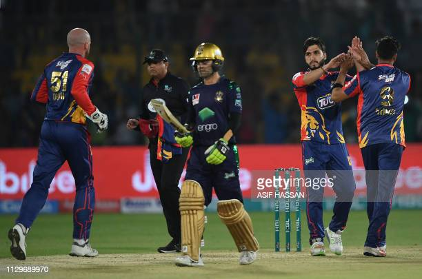 Cricketer Usman Shinwari of Karachi Kings celebrates with teammates after taking the wicket of Ahmed Shahzad of Quetta Gladiators while he walks back...