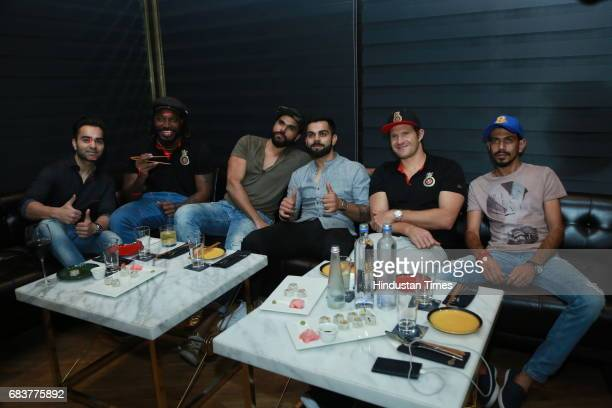 Cricketer Virat Kohli with his brother Vikas Kohli and Royal Challengers Bangalore teammates Chris Gayle Shane Watson and Yuzvendra Chahal during...