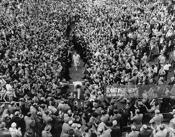 Cricketers Denis Compton and Bill Edrich and other players make their way through the vast crowd at the conclusion of the England v Australia Final...
