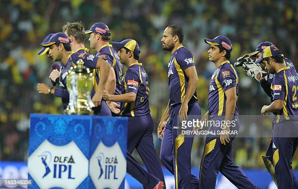 Cricketers from the Kolkata Knight Riders run past the DLF IPL trophy prior to the IPL Twenty20 cricket final match between Chennai Super Kings and...