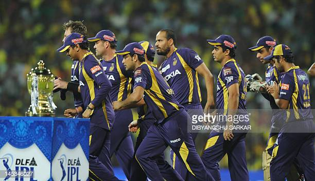 Cricketers Kolkata Knight Riders runs past the DLF IPL trophy prior to the IPL Twenty20 cricket final match between Chennai Super Kings and Kolkata...