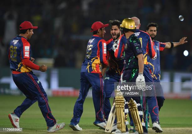 Cricketers of Karachi Kings celebrate the dismissal of Ahmed Shahzad of Quetta Gladiators as he walks back to the pavilion during the second match of...
