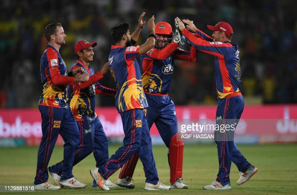 Cricketers of Karachi Kings celebrate the dismissal of Peshawar Zalmi cricketer Kieron Pollard during the fourth match between the Karachi Kings and...