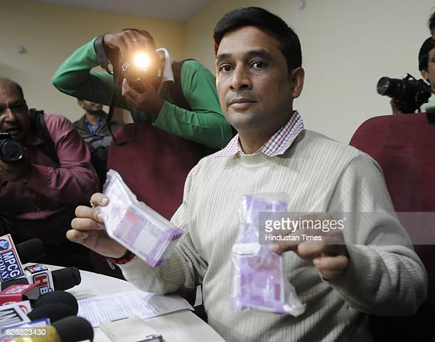 Crime Branch Shailendra Singh Chauhan showing new currency notes of Rs 746500 recovered from note smugglers on November 23 2016 in Bhopal India