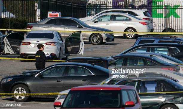 Crime lab technician works in the parking lot of the site of a mass shooting at a FedEx facility in Indianapolis, Indiana on April 16, 2021. - A...