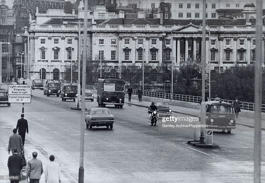 Crime London, England. 1968. The Kray Twins. Police cars escort a Black Maria van carrying Ronnie and Reggie Kray back to Brixton jail to be held on remand after a court hearing today. The Krays are charged with murder conspiracy charges. : News Photo