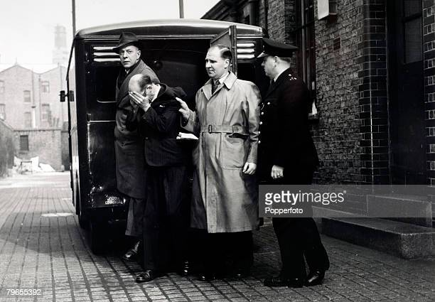 8th April 1953 West London John Christie aged 55 hides his face as he is led into West London Magistrates Court to face a charge of murdering his...