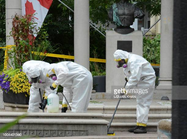 A crime scene clean up crew scrubs the side walks along Danforth Avenue at the scene of last night shooting in Toronto Ontario on July 23 2018...