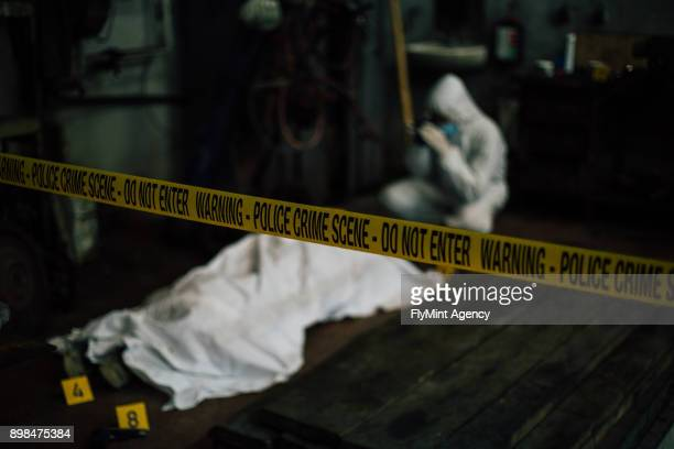 crime scene investigation - forensic investigating behind dead cover body and evidence - murder stock pictures, royalty-free photos & images