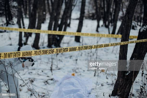 Crime scene investigation in a snow - forensic taking photos of a victim and evidence