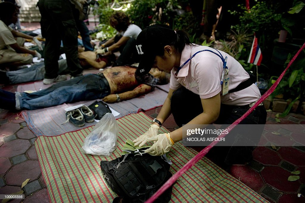 A crime scene investigator inspects the dead bodies of anti-government protesters killed in a gunbattle the day before lie on mats at a temple which had been turned into a shelter within an anti-government protest site in downtown Bangkok on May 20, 2010. Gunshots rang out near a Buddhist temple in the heart of an anti-government protest zone in Bangkok, and soldiers were advancing on foot along an elevated train track, an AFP photographer saw. Thai security forces stormed the 'Red Shirts' protest camp on May 19 in a bloody assault that forced the surrender of the movement's leaders who asked their supporters to disperse. AFP PHOTO/ Nicolas ASFOURI