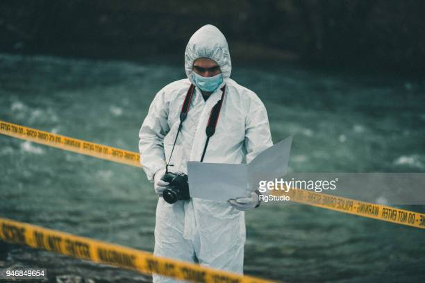 crime scene investigator looking at crime scene paperwork at the crime scene c - nasty c stock photos and pictures