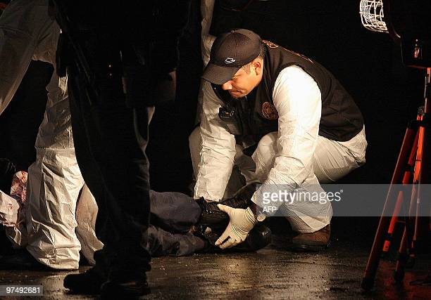 A crime scene investigator moves the corpse of a police officer laying on the street after a gang attack in San Nicolas de la Garza Nuevo Leon State...