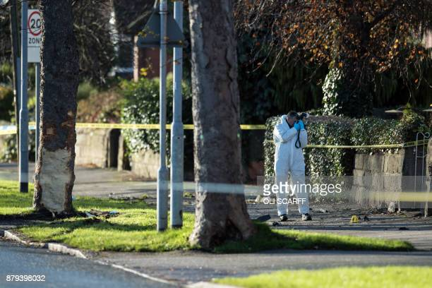 A crime scene investigator photographs the site of a car crash in which five people including three children were killed after a stolen car crashed...
