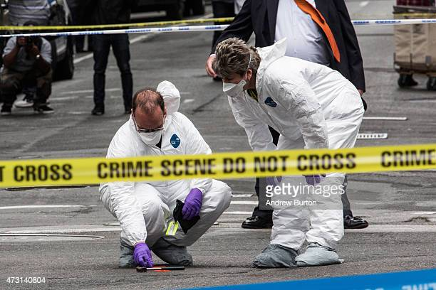 Crime scene investigators inspect a hammer used in an attack on a police officer on May 13 2015 in New York City The attacker was shot twice by a...
