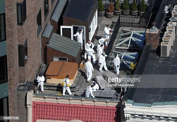 Crime scene investigators inspect a rooftop above the sight of a bombing on Boylston Street April 18 2013 in Boston Massachusetts Investigators...