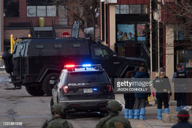 Crime scene investigators stand outside the entrance of the King Soopers grocery store in Boulder, Colorado after a mass shooting on March 22, 2021....