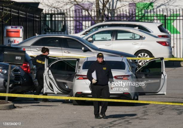 Crime scene investigators walk through the parking lot of the mass shooting site at a FedEx facility in Indianapolis, Indiana, on April 16, 2021. - A...