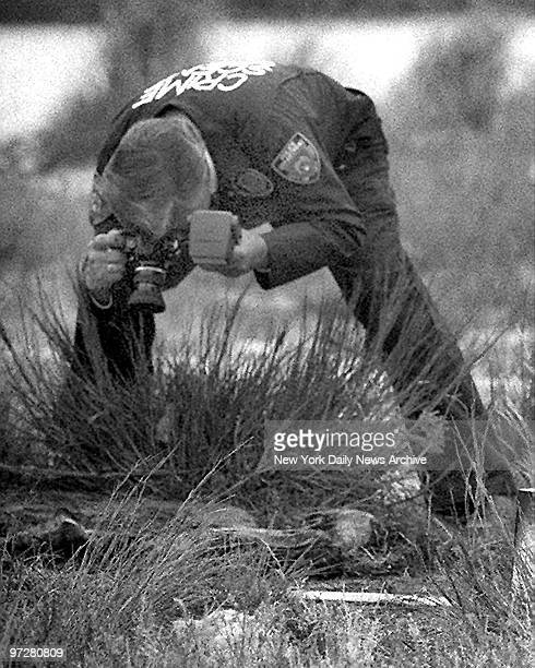 Crime scene photographer takes photos of remains of one of the victims of the serial killer Joel RIfkin