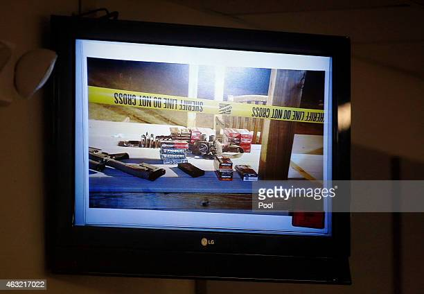 Crime scene photos from the Rough Creek Lodge and Resort where the deaths occurred are shown on television monitors during the capital murder trial...
