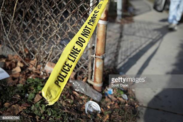 Crime scene tape clings to a fence where a Christmas Eve shooting left Derrick Jones and Stephen Tucker dead on December 27 2016 in Chicago Illinois...