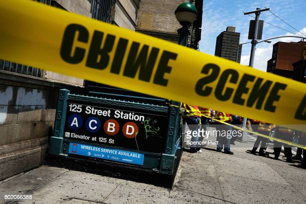 Crime scene tape is placed outside of a Metropolitan Transportation Authority Harlem subway station where a morning train derailment occurred on June...