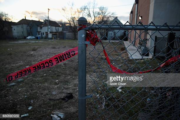 Crime scene tape remains in front of a vacant lot where a December 22 shooting left Richard Chamber dead on December 27 2016 in Chicago Illinois At...