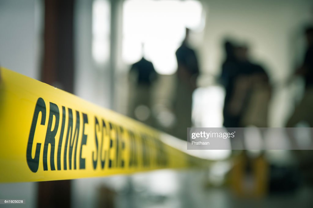 crime scene tape with blurred forensic in cinematic tone : Stock Photo