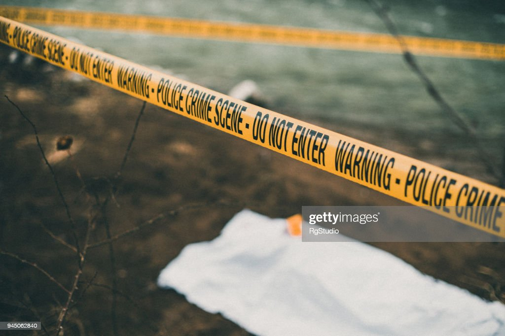 Crime scene with a police barricade tape : Stock Photo