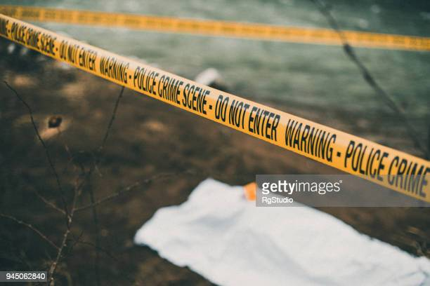 crime scene with a police barricade tape - dead body in water stock pictures, royalty-free photos & images