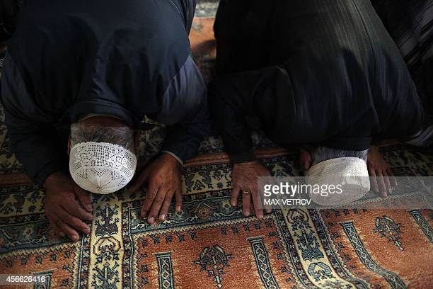 Crimean Tatar muslims pray in the Great Khan Mosque on the first day of the Eid alAdha in the city of Bakhchisaray on October 4 2014 Muslims...