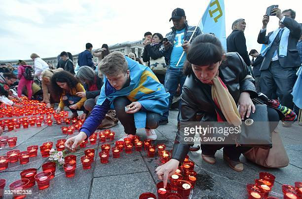 Crimean Tatars light candles during a memorial ceremony on the Independence square in Kiev on May 18 2016 in commemoration of the 72nd anniversary of...