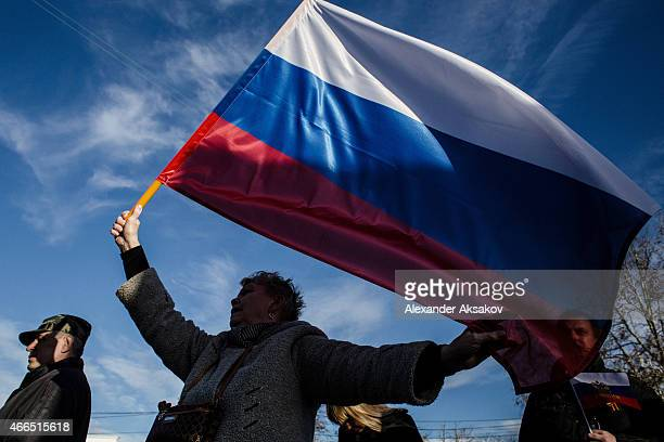 Crimeans wave Russian flags as they celebrate the first anniversary of the referendum on March 16 2015 in Sevastopol Crimea Today marks the first...