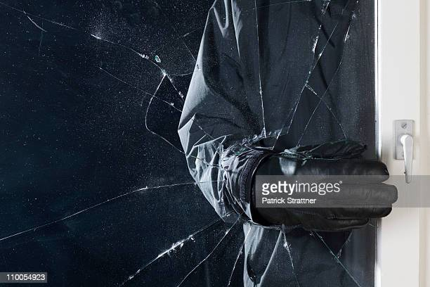a criminal breaking into a window, focus on hand - thief stock pictures, royalty-free photos & images