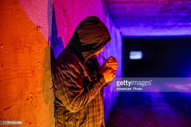 criminal drug addict smoking drugs in underground tunnel - smoking crack stock photos and pictures