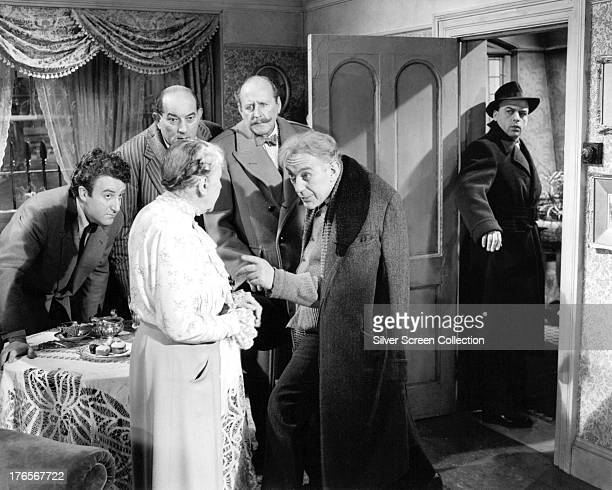 Criminal gang leader Professor Marcus played by Alec Guinness talks to his landlady Mrs Wilberforce while the rest of the gang look on in 'The...
