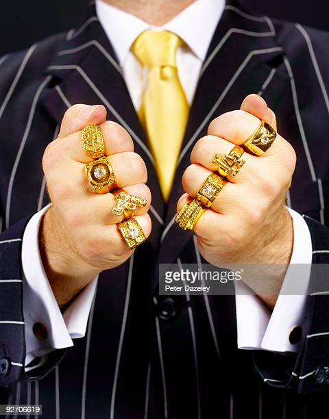 criminal in suit wearing gold rings. - bling bling stock pictures, royalty-free photos & images