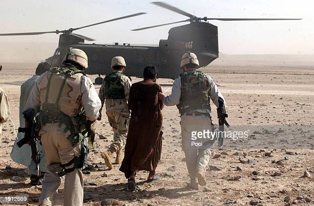 Criminal Investigation Task Force members escort a detainee April 9 2003 during Operation Resolute Strike in Helmand Province Afghanistan Operation...