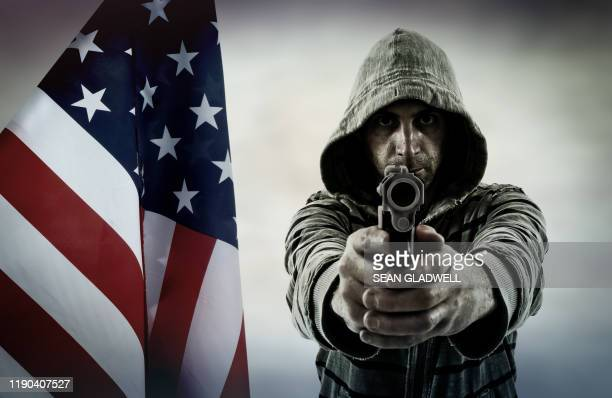 criminal pointing handgun with american flag - gun stock pictures, royalty-free photos & images