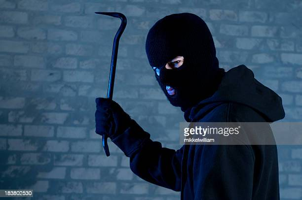 criminal raises crowbar ready to hit - burglar stock pictures, royalty-free photos & images