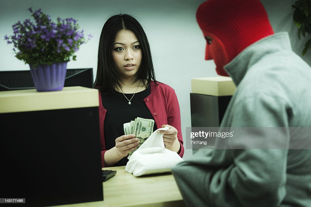 Criminal Robber Robbing an Asian Retail Bank Teller at Counter : Stock Photo
