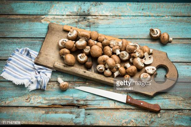 crimini mushrooms on wooden chopping board - edible mushroom stock pictures, royalty-free photos & images