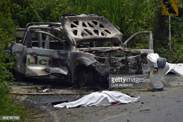 A criminology researcher inspects a burned police patrol truck surrounded by the bodies of the two policemen that died this Saturday after an attack...